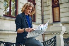 Jeune journal rougeâtre de lecture d'homme près du bâtiment de style ancien photos stock