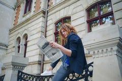Jeune journal rougeâtre de lecture d'homme près du bâtiment de style ancien images libres de droits