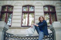 Jeune journal rougeâtre de lecture d'homme près du bâtiment de style ancien photo libre de droits