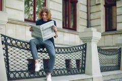 Jeune journal rougeâtre de lecture d'homme près du bâtiment de style ancien photo stock