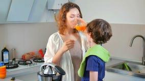 Jeune jus d'orange frais fait maison caucasien de mère et d'enfant dans la cuisine avec le presse-fruits électrique clips vidéos