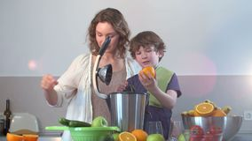 Jeune jus d'orange frais fait maison caucasien de mère et d'enfant dans la cuisine avec le presse-fruits électrique banque de vidéos
