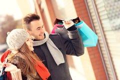 Jeune lèche-vitrines de couples dans la ville Photographie stock libre de droits