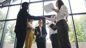 Jeune l'équipe ethnique multi sûre et attirante d'affaires rencontrent leurs collègues pour se serrer la main et l'échange banque de vidéos