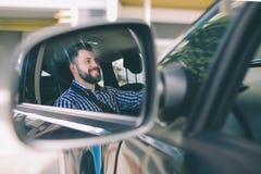 Jeune l'homme sérieux élégant aux cheveux foncés et barbu bel conduit une voiture images stock