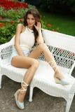 Jeune la dame élégante, snob et élégante avec le maquillage et la coiffure pose sur le sofa en osier en parc naturel photo stock