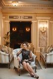Jeune la dame sexy et à la mode d'affaires dans la robe élégante s'assied dans des regards d'un fauteuil à l'appareil-photo et la photos stock