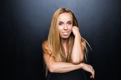 Jeune le modèle blond sexy et beau avec le corps mince pose dans le studio sur la chaise, mur foncé sur le fond Image libre de droits
