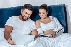 Jeune lecture affectueuse de couples dans le lit image stock
