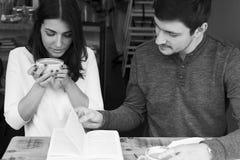 Jeune lecture de couples dans le café Photo libre de droits