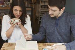 Jeune lecture de couples dans le café Photographie stock libre de droits