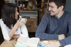 Jeune lecture de couples et sourire dans le café Photographie stock libre de droits
