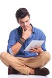 Jeune lecture occasionnelle inquiétée d'homme sur un comprimé Images libres de droits
