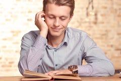 Jeune livre de lecture beau d'homme en café Photos libres de droits