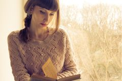 Jeune livre de lecture de femme adulte près de la fenêtre Photo stock