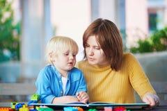 Jeune livre de lecture de mère à son fils image libre de droits