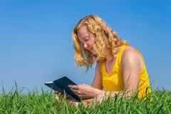Jeune livre de lecture néerlandais de femme en nature Photographie stock libre de droits