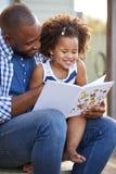 Jeune livre de lecture noir de père et de fille dehors photographie stock libre de droits