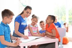 Jeune livre de lecture volontaire avec des enfants photo libre de droits