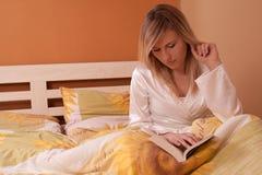 Jeune livre de relevé blond de femme dans le bâti Photos stock
