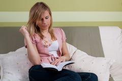 Jeune livre de relevé de femme de beautifull sur le sofa Photos libres de droits
