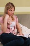 Jeune livre de relevé de femme de beautifull sur le sofa Images libres de droits