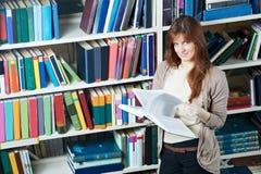 Jeune livre de relevé de fille d'étudiant dans la bibliothèque Photographie stock libre de droits