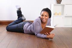 Jeune livre de relevé heureux d'étudiant féminin à la maison Photographie stock libre de droits