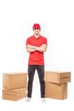 Jeune livreur beau avec des boîtes et des mains croisées sur le blanc photographie stock