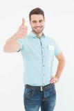 Jeune livreur heureux faisant des gestes des pouces  Image stock