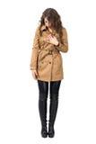 Jeune longue femme de cheveux tenant le manteau beige regardant vers le bas photo stock