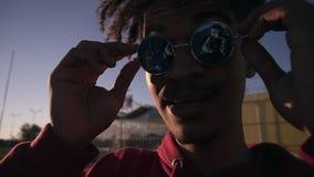 Jeune mâle à la peau foncée élégant utilisant les nuances à la mode et la chemise rouge - participation alors mise sur les lunett banque de vidéos
