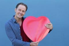 Jeune mâle adulte de sourire dans l'équipement occasionnel tenant un grand coeur avec ses mains Photographie stock libre de droits