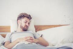 Jeune mâle américain beau dormant dans le lit à la maison image stock