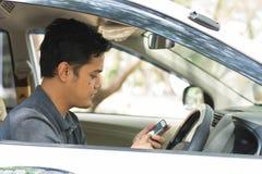 Jeune mâle asiatique attirant à l'aide du téléphone portable conduisant sa voiture dans le jour ensoleillé photographie stock