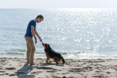 Jeune mâle caucasien jouant avec le chien sur la plage Homme et chien ayant l'amusement sur le bord de la mer Photographie stock