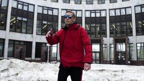 Jeune mâle dans des danses rouges de vêtements et de lunettes de soleil de sport à côté du grand bâtiment gris banque de vidéos