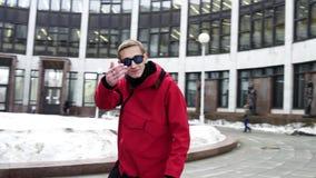 Jeune mâle dans des vêtements rouges de sport et des mouvements et des regards de lunettes de soleil à la caméra banque de vidéos