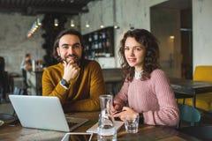 Jeune mâle de hippie et ordinateur portable fonctionnant femelle ensemble en café Photographie stock libre de droits