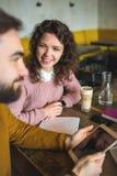 Jeune mâle de hippie et ordinateur portable fonctionnant femelle ensemble en café Image stock