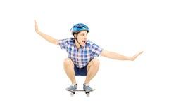 Jeune mâle de sourire avec le casque patinant sur un panneau de patin Photos stock