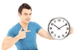 Jeune mâle de sourire se dirigeant avec sa main sur une horloge murale Image libre de droits
