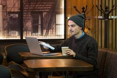 Jeune mâle discutant ou parlant au-dessus de l'Internet dans un café photos libres de droits