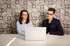 Jeune mâle et associés féminins s'asseyant derrière un moniteur d'ordinateur et pensant à quelque chose image stock