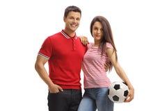 Jeune mâle et pose femelle avec un football image stock