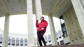 Jeune mâle frais habillé dans la veste rouge et des lunettes de soleil frappant avec émotion banque de vidéos