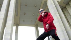Jeune mâle frais utilisant la veste rouge et les lunettes de soleil frappant avec émotion clips vidéos