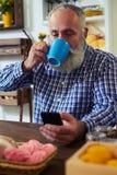Jeune mâle heureux heureux prenant une petite gorgée de café tout en tenant a Photographie stock libre de droits