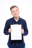 Jeune mâle joyeux positif montrant le presse-papiers vide et le sourire Photographie stock libre de droits