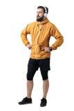 Jeune mâle sûr dans la veste de port pulsante d'anorak de vêtements de sport avec des mains sur des hanches regardant loin image libre de droits